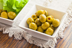 Olives are in two white bowls with leaves Stock Photography