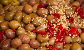 Olives vertes avec le poivre d'un rouge ardent. Photographie stock libre de droits