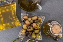 Olives vertes et noires avec des bouteilles d'huile d'olive Photo stock