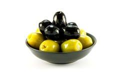 Olives vertes et noires dans une cuvette Image libre de droits