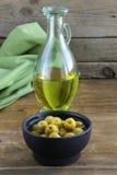 Olives vertes marinées et une bouteille d'huile Images libres de droits