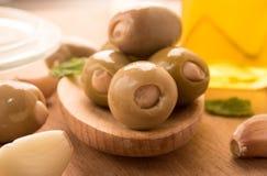 Olives vertes sur une cuillère en bois garnie avec le basilic, ail Image stock