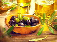 Olives and virgin olive oil. On the wooden table Royalty Free Stock Photos