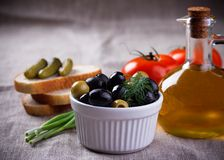 Olives in white bowl and small bottle of olive oil on jute fabric Stock Photos