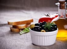 Olives in white bowl and small bottle of olive oil on jute fabric. Bread, red tomatoes, black and green olives in white bowl and small bottle of olive oil on Stock Image