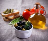 Olives in white bowl and small bottle of olive oil on jute fabric Stock Images