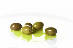 Olives on a white plate. Olives in olive oil on a white plate Stock Images