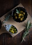 Olives on wood aged in close-up in Zenith shot. Olives in  containers with rustic bottom Royalty Free Stock Images
