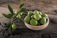 Olives into wood pot on an old wooden table Royalty Free Stock Photography