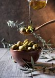 Olives in wooden spoon pouring oil over bowl full of olives with bone royalty free stock image