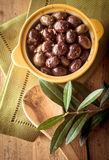 Olives on Wooden Table with Branch and Napkins Stock Images