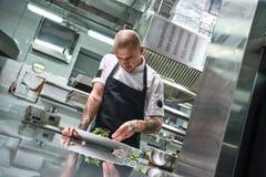 olivgrön för olja för kök för kockbegreppsmat ny över hällande restaurangsallad Stående av den stiliga yrkesmässiga kocken i svar arkivfoton