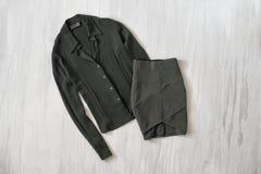 Olivgrön grön blus och kjol på träbakgrund Innegrej c royaltyfri foto