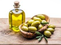Olivgröna bär och flaska av olivolja på trätabellen royaltyfria foton