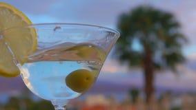 Olivgröna nedgångar in i ett exponeringsglas med martini och citronen stock video