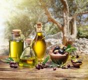 Olivgrüne Beeren in der hölzernen Schüssel und in den Flaschen des Olivenöls auf Stockfotografie