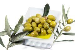 Olivgrüne Frucht und Blätter getränkt im Olivenöl Stockfoto