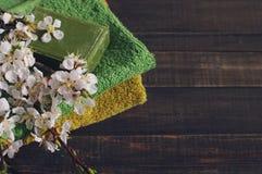 Olivgrüne Seife auf einem Tuch mit Frühlingsblumen einer Aprikose Lizenzfreie Stockfotos