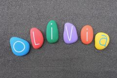 Olivia, feminine given name with multicolored painted stones over black volcanic sand Royalty Free Stock Images