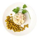 olivier的沙拉,在与裁减路线的白色背景隔绝的板材的绿豆 免版税库存照片