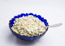 Olivier salad. In a blue glass bowl Royalty Free Stock Photography