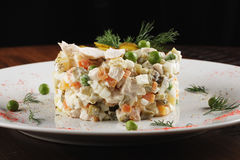 Olivier salad with chicken. In a white plate. Wooden background Royalty Free Stock Photo
