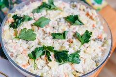 Olivier-salade met greens in een grote kom wordt verfraaid die Stock Foto