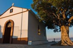 Olivo y la iglesia de Agios Ioannis Kastri en la puesta del sol, famosa de las escenas de la película de Mia de la mama, isla de  Imágenes de archivo libres de regalías