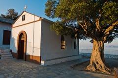 Olivo y la iglesia de Agios Ioannis Kastri en la puesta del sol, famosa de las escenas de la película de Mia de la mama, isla de  Imagen de archivo libre de regalías