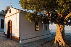 Olivo y la iglesia de Agios Ioannis Kastri en la puesta del sol, famosa de las escenas de la película de Mia de la mama, isla de  Fotos de archivo libres de regalías