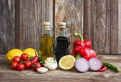 Olivolja, balsamic vinäger och grönsaker på gammal träbakgrund Arkivfoto