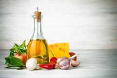 Olivolja med kryddor och grönsaker på träbräde arkivfoto