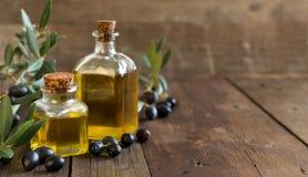 Olivolja och nya oliv på wood bakgrund Arkivbild