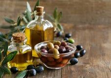 Olivolja och oliv på wood bakgrund Royaltyfria Foton