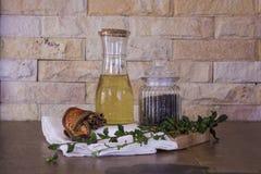 Olivolja och svartpeper på skärbräda- och tegelstenbakgrund Arkivbild