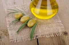 Olivolja på en trätabell Arkivbilder