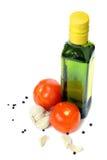 Olivolja, vitlök, peppar och grönsaker över vit Arkivfoton