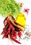 Olivoljaflaska, örter, vitlök och grönsaker på vitt träb Arkivfoto