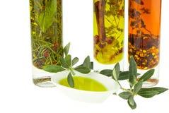 Olivoljaflaska och bunkeplatta med den olivgröna filialen Jungfrulig olivolja Naturlig olivolja, sund mat Arkivfoto
