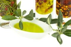 Olivoljaflaska och bunkeplatta med den olivgröna filialen Jungfrulig olivolja Naturlig olivolja, sund mat Arkivfoton