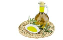 Olivoljaflaska och bunkeplatta med den olivgröna filialen Jungfrulig olivolja Naturlig olivolja, sund mat Arkivbilder