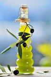Olivoljaflaska och nya oliv Arkivbild