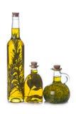 Olivoljaflaskor med aromatiska örter Fotografering för Bildbyråer