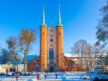 Oliwa Cathedral in winter. GDANSK OLIWA, POLAND - JANUARY 16, 2017: People on catheral square covered snow at sunny winter day Stock Images