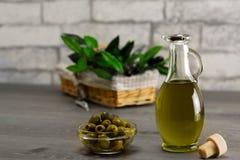 Oliwa z oliwek i gałązka oliwna na drewnianym stole obraz royalty free