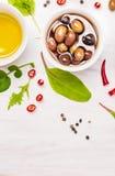 Oliwki i olej w białym pucharze z pikantność i ziele na drewnianym Zdjęcie Royalty Free