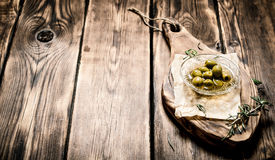 Oliwki w oleju i rozmarynów gałąź na desce Zdjęcia Stock