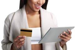 Oliwkowa murzynka trzyma cyfrowego pastylka komputer, wynagrodzenie od złocistej kredytowej karty i blisko lily farbuje miękki na Zdjęcie Stock