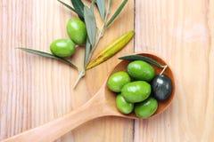 Oliwna zieleń i czerń w drewnianej łyżce Obraz Stock
