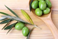Oliwnej zieleni gałąź na drewnianym stole i liście Fotografia Stock